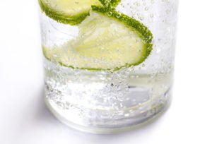 Lime slices, ice and soda in glass on white background.