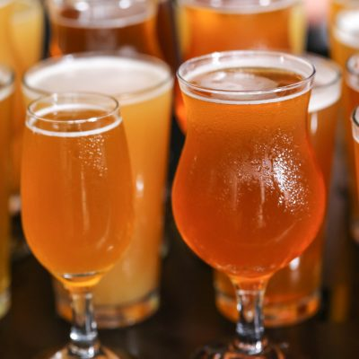 A crowd of craft beer glasses filled with a variety of different sour beer styles.