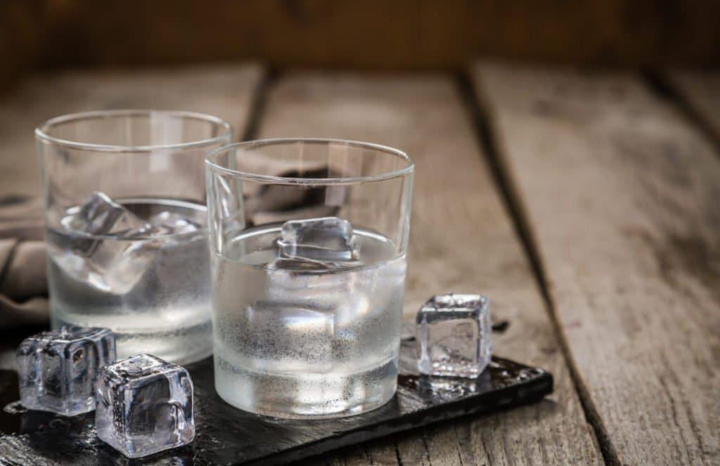 Vodka in shot glasses on rustic wood background