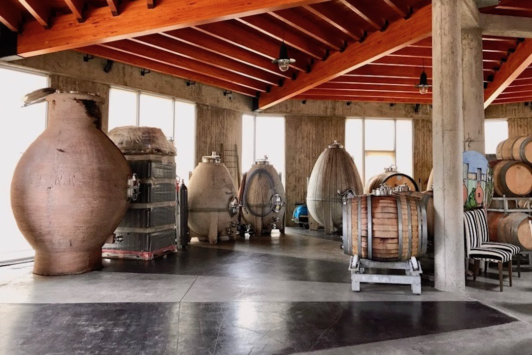 View inside SuperUco Winery with concrete urns, eggs and wood barrels