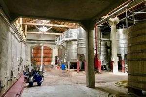 View inside an Argentinean winery showing concrete tanks, stainless steel tanks and oak barrels