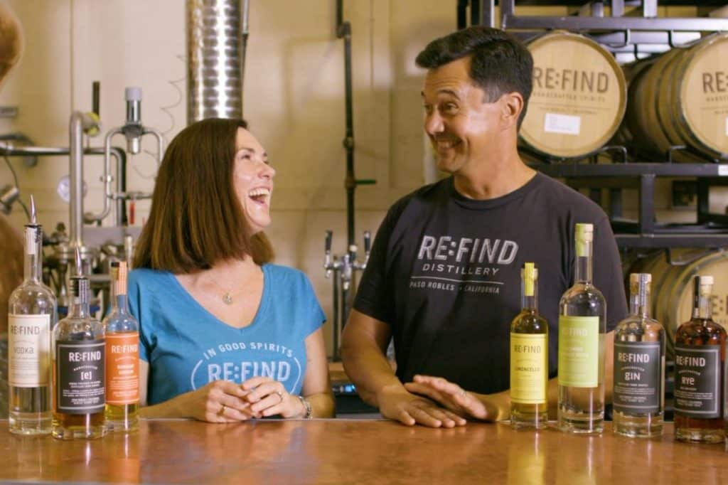 Alex and Monica of Re:Find Spirits laughing over vodka and spirits at their tasting bar
