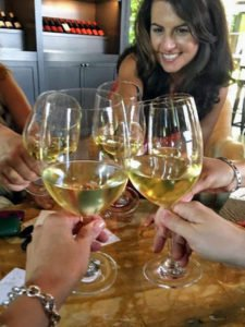 Suzane cheersing white wine glasses with others