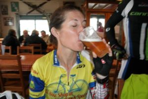Bio picture of Jill drinking a beer after a bike ride in the Alps