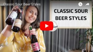 Video opening shot of Suzanne holding up the 3 sour beers she'll cover in the Classic Sour Beer Styles video