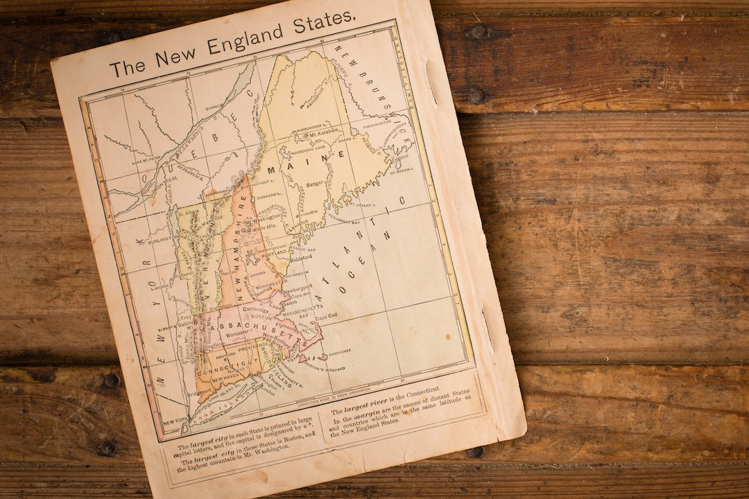 Color image of an old map of the New England States, from 1867, sitting slanted on wood background