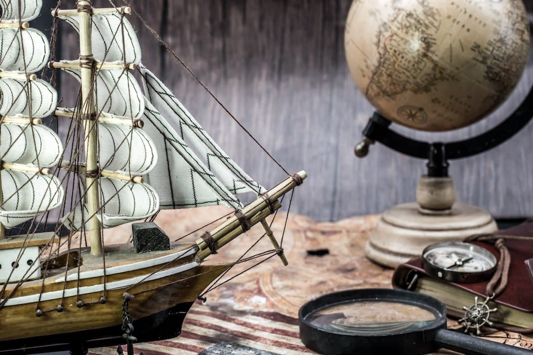 old world map with a ship, globe, magnifying glass and other explorer tools