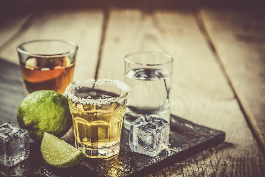 The three types of tequila in shot glasses side by side on rustic wood background