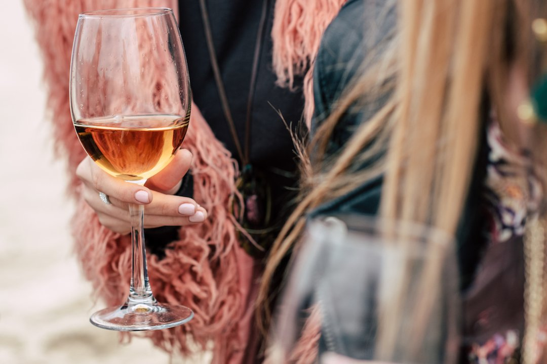 Close-up view of female hands holding glasses with rosé wine outdoors