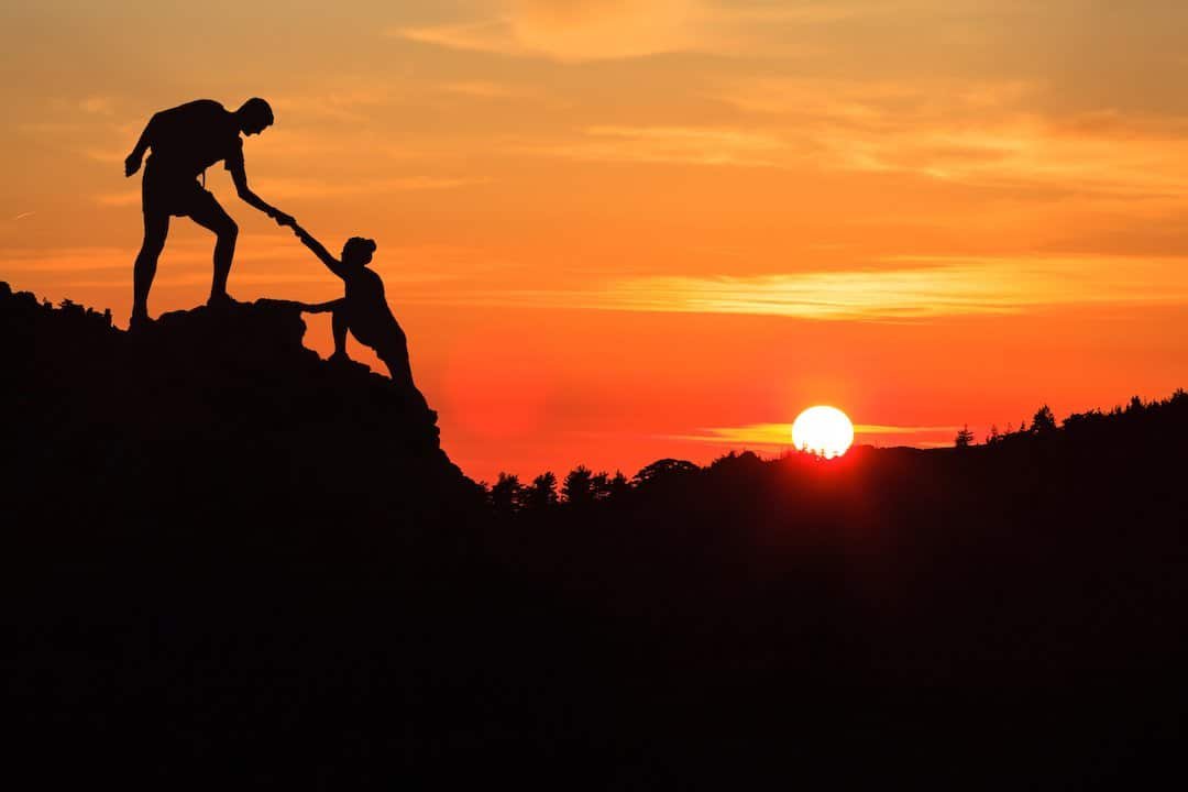 Teamwork - helping hand trust silhouette in inspiring mountains with orange light.