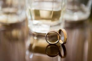 Wedding rings with cider in the background