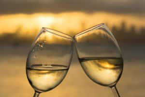 Clinking white wine glasses at sunset