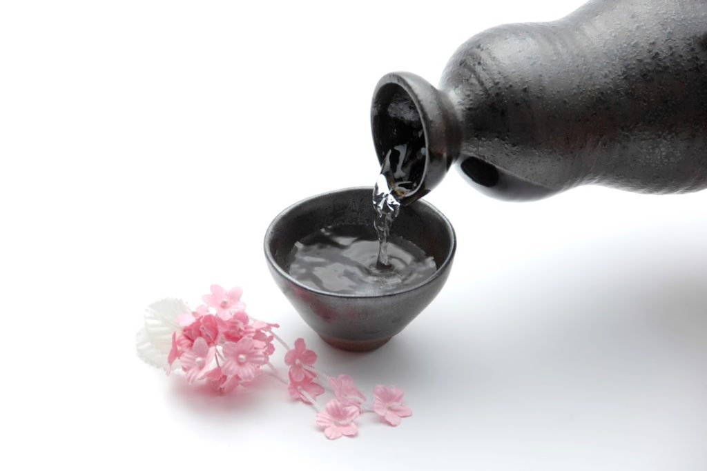 Sake pouring from a black ceramic carafe into a black ceramic cup with cherry blossoms on a white table