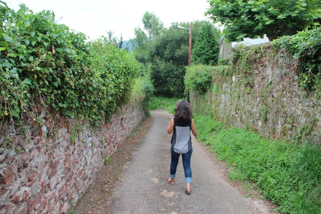 Suz walking down a stone wall pathway in Asturias