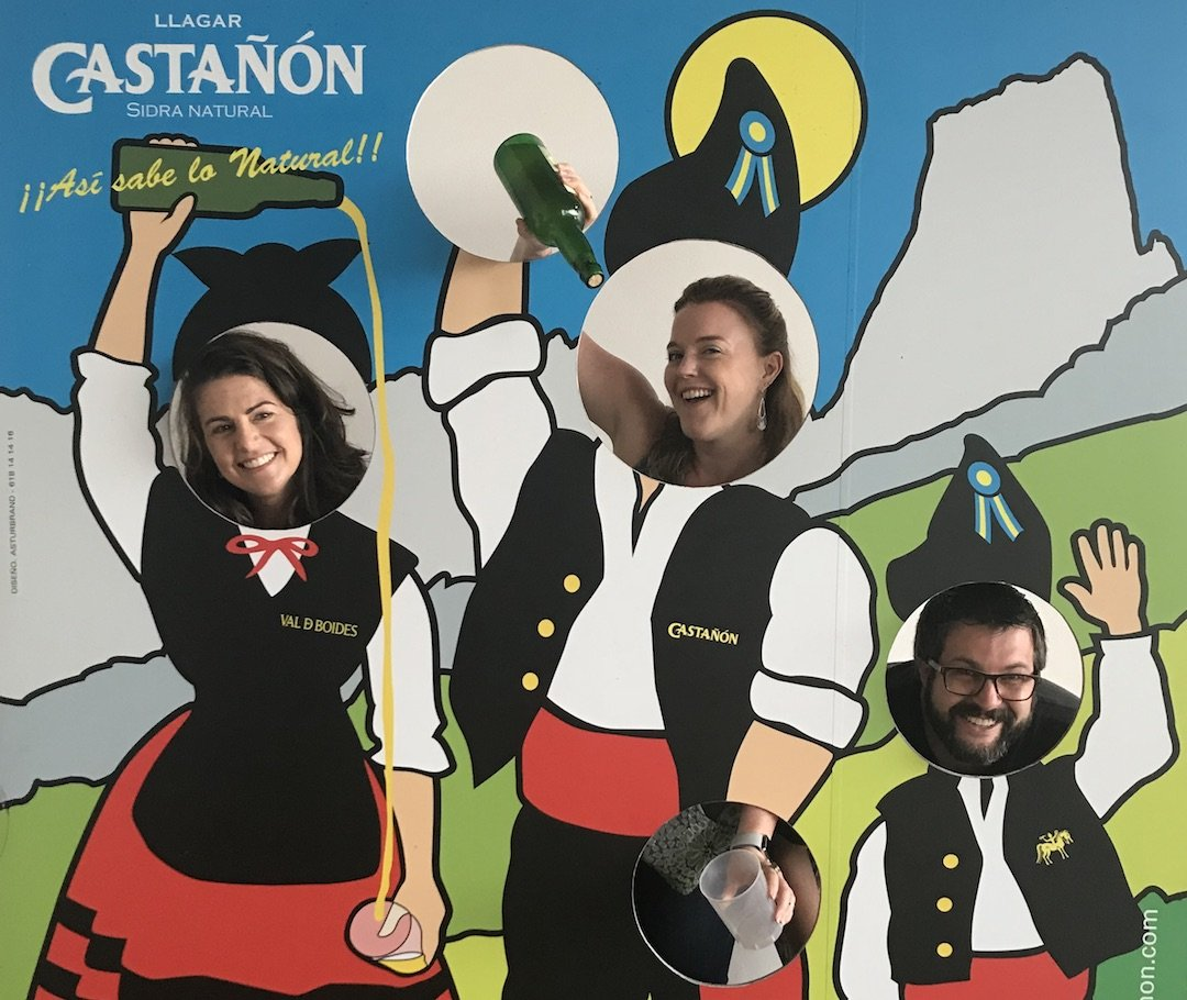 Suz and her two friends in a carnival cutout of us pouring cider in traditional Asturian clothes