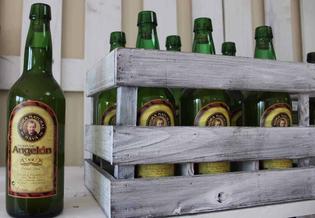 An example of sidra natural from one producer - one bottle with a wooden box full of bottles next to it.