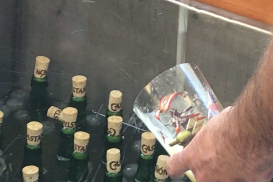 Sidra pouring over bottles with corks partially removed