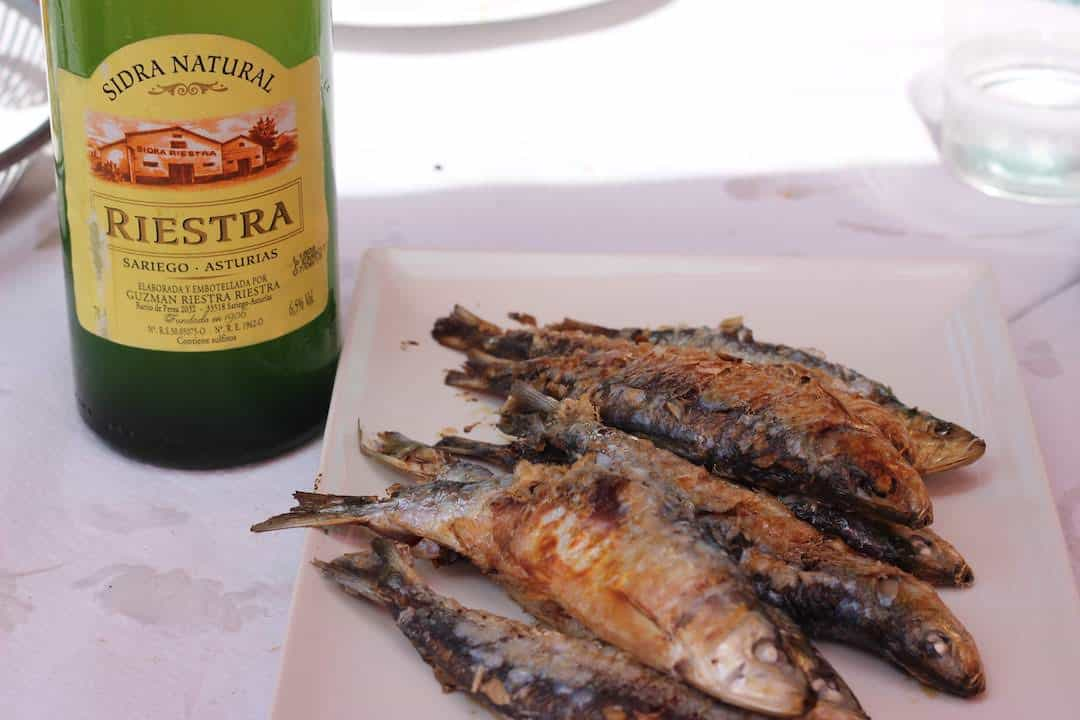 Sidra and grilled sardines on a restaurant table