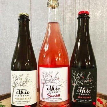 Three Bottles of Ethic Cider that are part of the holiday box on a barrel against a light background