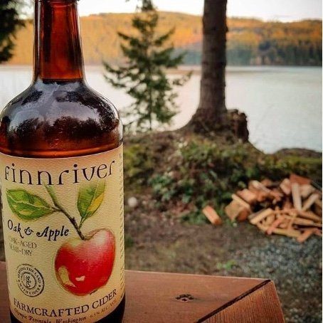 Finn River Oak and Apple Cider On a Picnic Table with a Woodland Scene Behind
