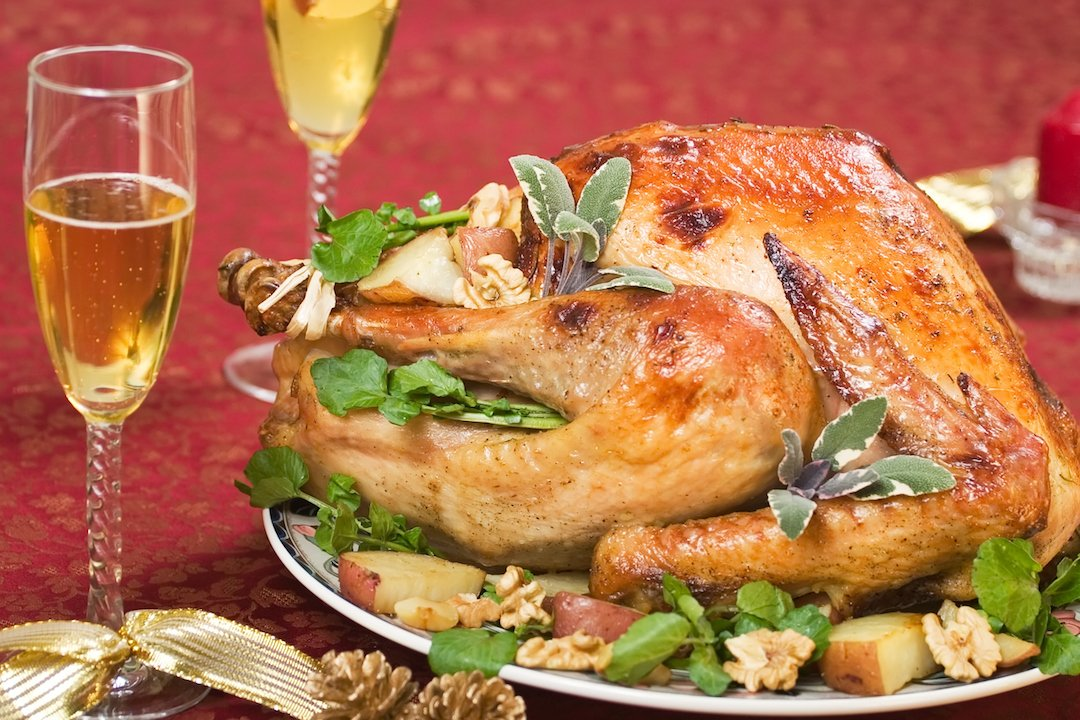 Garnished turkey on a holiday decorated table with candle and flutes of cider