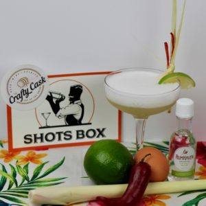 Image of the Tom Kha-ocktail on a tropical landscape with ingredients around it