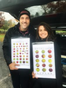 Eric and Suz holding 2 of Eric's amazing apple posters in the back of their car on their road trip