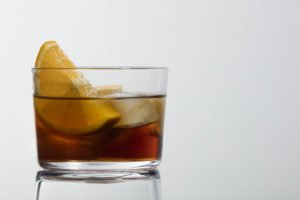 Classic glass of red vermouth with ice and orange slice on a white background with a beautiful reflection