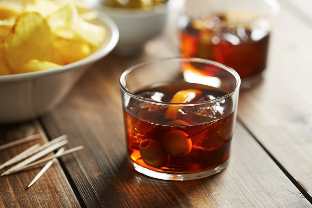 Spanish vermouth with orange slice and olives and nibbles alongside it
