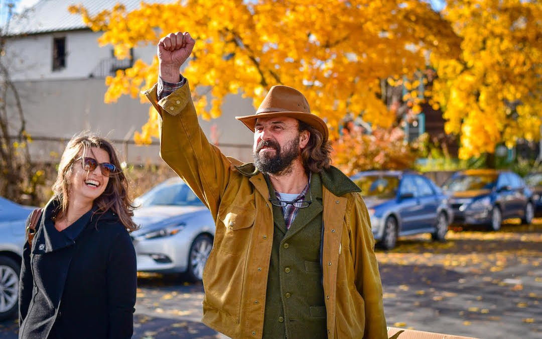 Suz and Westwind Ciders cidermaker Fabio enthusiastically talking shop while walking down a street with Fall Foliage