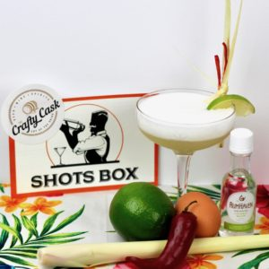 Tom Kha-cktail with ingredients/bottles displayed on a tropical background with Shots Box and The Crafty Cask logos