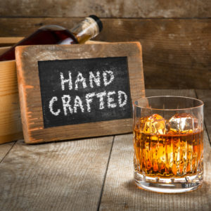 Craft spirits store - image of Barrel aged craft liquor spirits glass ice bourbon whisky scotch brandy rum on wood bar table Hand crafted small batch with sign