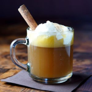 Hot Buttered Rum in a glass mug with added whipped cream and a cinnamon stick on a napkin on a wood table