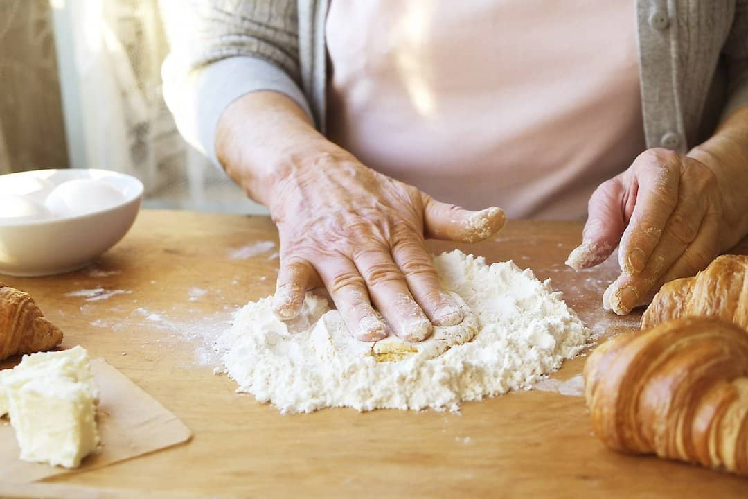 Elderly woman cooks french croissants, bare wrinkled hands, ingredients, soft warm morning light,top view