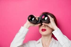Social Media Helps Consumers Find You - woman looking through binoculars against a pink background
