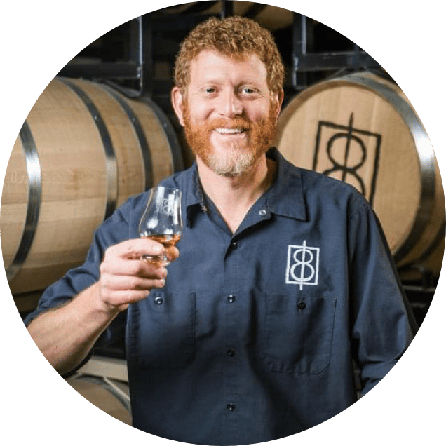 Craft spirits maker at One Eight distillery holding glass of whiskey
