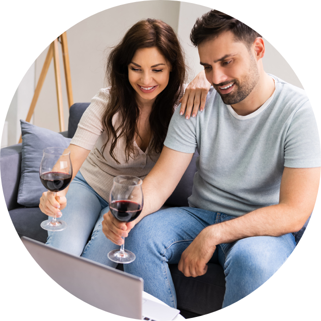 Couple holding wine glasses in front of computer during virtual event