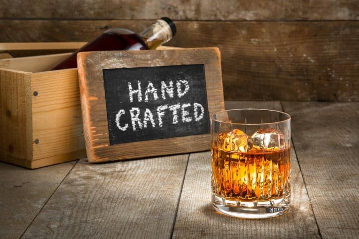 Glass of whiskey in front of sign reading Hand Crafted