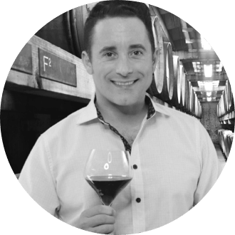 Portrait of Evan Rothrock holding wine glass at winery