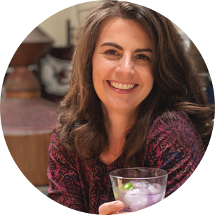 Portrait of Suzanne with cocktail at distillery