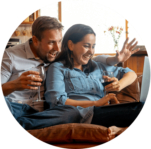 Couple on couch, laughing while drinking wine during virtual event on computer