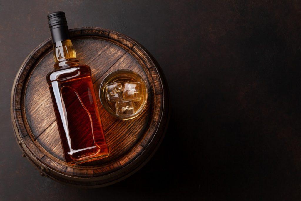 bourbon bottle on a barrel